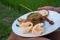Nasi goreng, traditional Indonesian dish served with prawn crackers and chicken satay on white plate