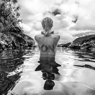 Naked woman bathing and relaxing in natural swimming pool in black and white.