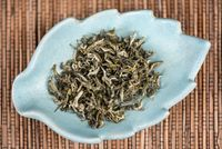 Tea dried leaves in a white cup