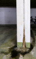 water damage in concrete construction with calcium and rust deposits and puddles
