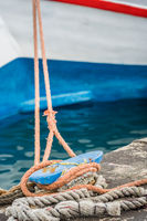 Boat anchored to a bollard with ropes