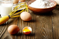Raw organic brown chicken broken eggs with yolk flour milk and whisk on kitchen wooden table