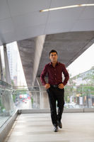 Young handsome Hispanic businessman walking and thinking on the footbridge