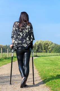 Disabled woman walks on crutches in dutch nature