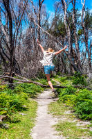 Girl outdoors jumping over tree fallen across track
