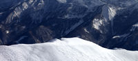 Panoramic view on snowy off piste slope with traces from skis and snowboarding