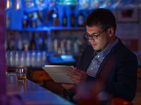 Businessman with tablet pc and whisky at the bar counter