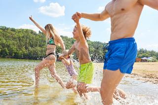 Familie beim Baden im See im Sommerurlaub