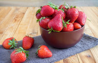 Strawberries on the table in a ceramic bowl.