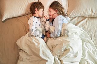 Bruder und Schwester im Bett albern fröhlich