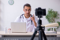 Young male doctor recording video for his blog