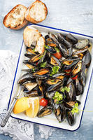 Traditional barbecue Italian blue mussel with baguette and tomatoes in white wine as top view on a tray