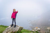 Happy girl on the top of  large rock