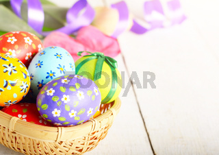 Rustic style painted easter eggs in basket on white table