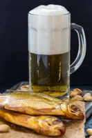 Glass of beer, smoked fish and pistachios.