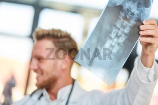 Junger Arzt in der Orthopädie mit Röntgenbild