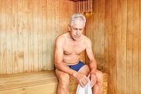 Alter Mann sitzt erschöpft in der Sauna