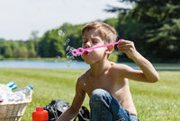 Boy enjoys blowing soap bubbles