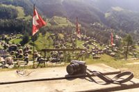 a vintage looking photo camera on a wooden table on a view point on alpine village in Swiss Alps - s