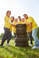 Glückliches Team steht an einem Stapel Reifen