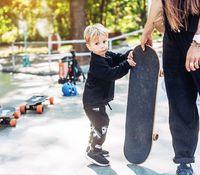 little boy carries a big skateboard outside