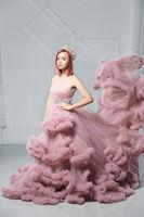 Beautiful young redhead woman posing in a studio.