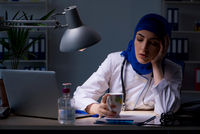 Arab female doctor working in the clinic at night