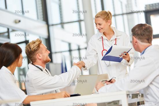 Junge Ärztin begrüßt einen Kollegen mit handshake