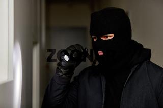 Einbrecher nachts mit Taschenlampe und Sturmhaube