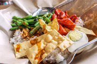 A traditional malay curry paste rice dish nasi lemak served on a paper with chips
