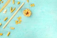 Italian pasta variety, flat lay banner, shot from above on a blue background with copy space
