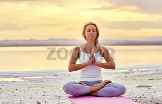 Aged woman sitting in lotus position do meditation on nature during sunset
