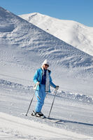 Skier downhill on snowy ski slope at nice sun day
