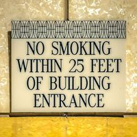 Square frame No smoking sign against the shiny white and golden wall of a building