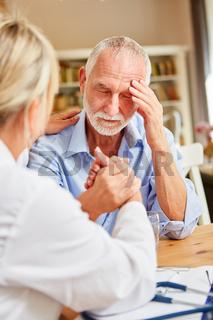 Ärztin tröstet Senior Patient mit Depression