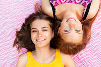 smiling teenage girls lying on picnic blanket