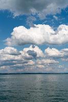 vertical background of flat anvil-like cumulus clouds in blue sky and blue lake below