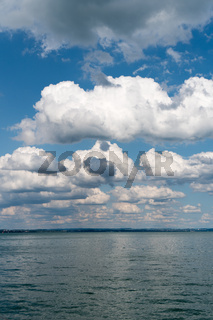 vertical background of flat anvil-like cumulus clouds in blue sky and blue lake below