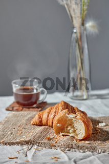Morning breakfast still life with fresh croissants and coffee cup on a gray.