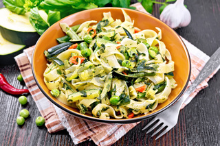 Tagliatelle with green vegetables on wooden board