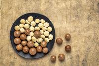 macadamia nuts on a black plate