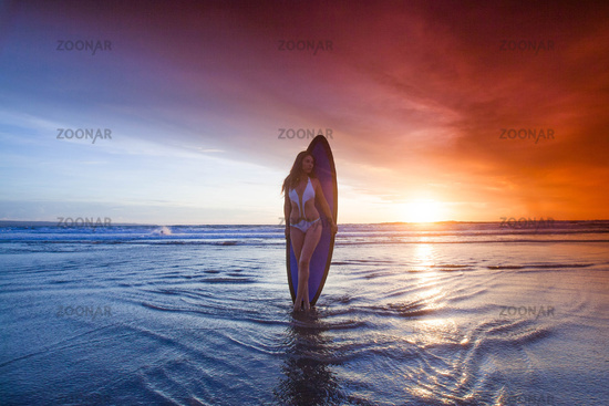 Surfer woman on beach at sunset