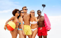 happy friends taking selfie on summer beach