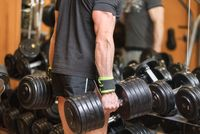 close up of muscular man holding heavy dumbbell  in gym.