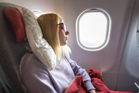 Tired blonde casual caucasian lady sleepin on seat while traveling by airplane. Commercial transportation by planes.
