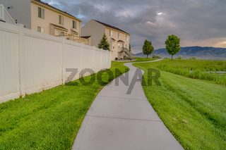 Paved walkway in front of homes with view of a pond and vast grassy terrain