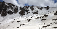 Panoramic view on mountains with snow cornice and avalanche trail
