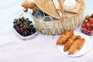 picnic basket, food and wine glasses on blanket