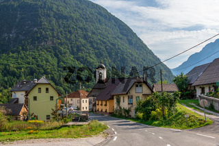 Street Scenario of Village Log pod Mangartom from north direction of predil pass with Julian Alps. Bovec, Slovenia, Europe.