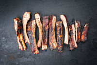 Barbecue spare ribs St Louis cut with hot honey chili marinade sliced as top view on an old rustic board with copy space